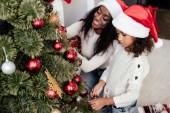 africká americká matka a dcera v santa claus klobouky dekorační stromečky společně doma