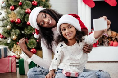 african american family in santa claus hats taking selfie on smartphone in decorated room at home, christmas holiday concept