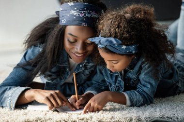 portrait of african american woman helping daughter doing homework on floor at home