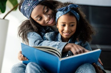 portrait of african american mother and daughter looking at family photo album at home