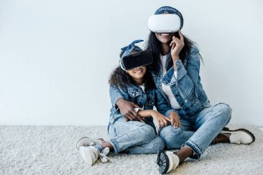 african american mother hugging daughter in similar clothing and vr headsets at home