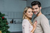 portrait of smiling young affectionate couple looking at camera at home