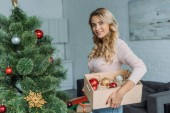 atraktivní dívka zdobení vánočního stromku a hospodářství box s ozdoby doma, při pohledu na fotoaparát