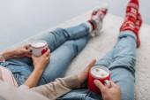 Fotografie Oříznout obrázek pár drží šálky cappuccina a sedí na koberci doma