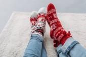 Fotografie oříznutí obrazu, kterou pár sedí na koberci v džínách a vánoční ponožky