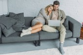 Photo affectionate couple watching something on laptop on sofa in living room