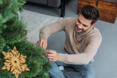 high angle view of smiling handsome man decorating christmas tree with baubles and sitting on floor at home