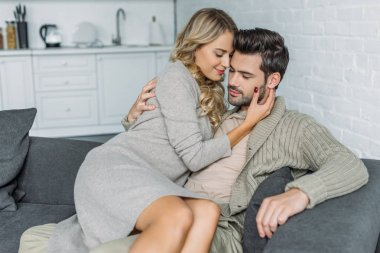 beautiful young woman embracing her boyfriend while sitting on him on couch at home