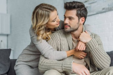 attractive young woman embracing her boyfriend on couch at home