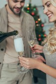 Fotografie schöne junge Paar gießt Champagner in Gläser vor Weihnachtsbaum zu Hause