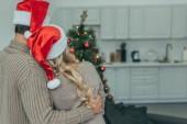 vista posteriore delle coppie in cappelli della santa che esamina lalbero di Natale a casa