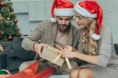 Fotografie junges Paar in Santa Hüte dekorieren Weihnachtsgeschenk zusammen zu Hause konzentriert
