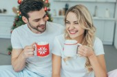 Fotografie laughing young couple with cups of cocoa sitting in bed at home on christmas