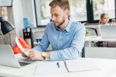 mladý podnikatel drží papíry a práci s přenosným počítačem v kanceláři