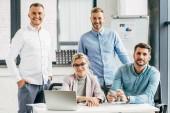 professionelles junges Business-Team lächelt während der gemeinsamen Arbeit im Büro in die Kamera