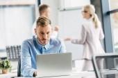 koncentrált fiatal üzletember laptop és Office mögött dolgozó kollégák segítségével