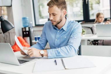young businessman holding papers and working with laptop in office