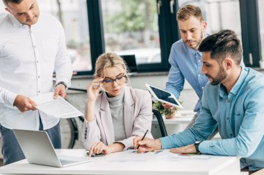 young businesswoman in eyeglasses working with male colleagues in office
