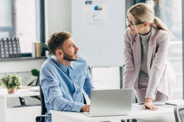 young businessman and businesswoman talking and looking at each other while working with laptop in office