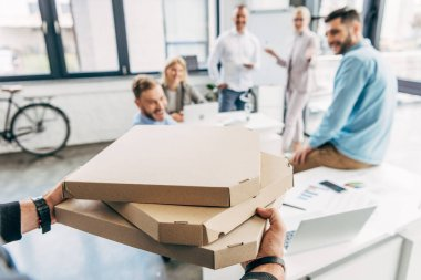 cropped shot of man bringing pizza to happy colleagues in office