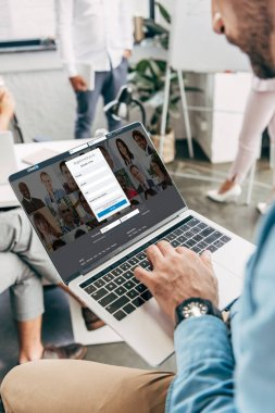 cropped shot of young businessman using laptop with linkedin website on screen