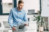 vážný mladý podnikatel drží papíry a sedí na stole v kanceláři