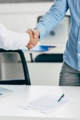 Photo cropped shot of businessmen shaking hands above table with contract