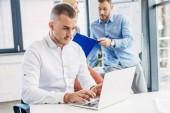 fiatal üzletember laptop és Office mögött dolgozó kollégák segítségével