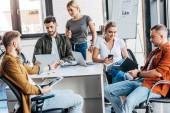 Skupina mladých neformální obchodní lidí pracujících s miniaplikacemi spolu v kanceláři
