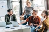 Skupina mladých podnikatelů mluvil při práci na startu spolu v kanceláři