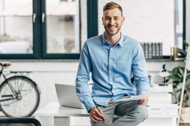 handsome young businessman holding papers and smiling at camera in office