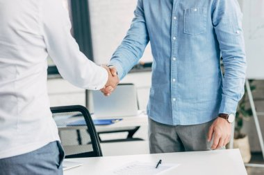 cropped shot of businessmen shaking hands at workplace