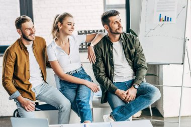 group of smiling young business people looking away together at office