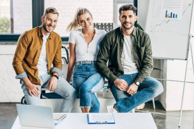 group of smiling young business people looking at camera together at office