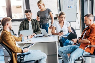 group of young casual business people working with gadgets together at office