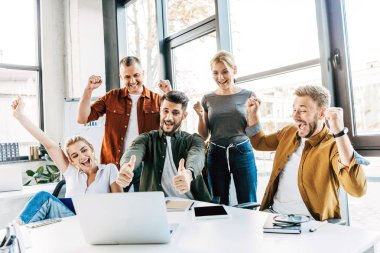 Group of young successful entrepreneurs celebrating victory and showing thumbs up at office and looking at camera stock vector