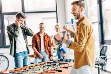 expressive casual business people playing table football at office and having fun together