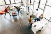 pohled z vysokého úhlu skupiny mladých podnikatelů pracuje na spuštění a baví spolu v kanceláři