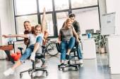Fotografie Gruppe junger Geschäftsleute reitet auf Stühlen im modernen Büro