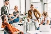 Skupina mladých podnikatelů chatování při práci na startu spolu v kanceláři