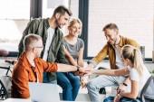Skupina happy mladých podnikatelů dělat tým gesto, zatímco spolupracují na startu v kanceláři