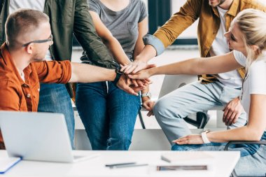 Cropped shot of group of young entrepreneurs making team gesture while working on startup together at office stock vector