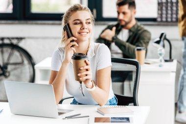telefonla konuşurken ve meslektaşım arka plan üzerinde ofisindeki kahve içme çekici genç kadın