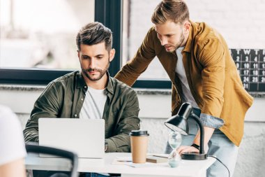 handsome young businessmen working with laptop together at office