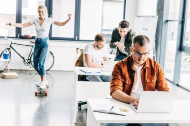 group of young progressive entrepreneurs working on startup together at modern open space office while woman riding skateboard on background