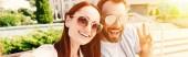 panoramatický pohled šťastné přítel a přítelkyně v pohledu kamery v městě, člověk ukazuje znamení míru sluneční brýle