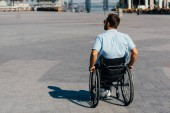 Fotografie back view of man in sunglasses using wheelchair on street