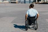 Rückansicht eines Mannes mit Sonnenbrille im Rollstuhl auf der Straße
