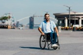 Fotografie gut aussehender Mann mit Sonnenbrille im Rollstuhl auf der Straße