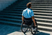 Fotografie back view of man using wheelchair on street and looking at stairs without ramp